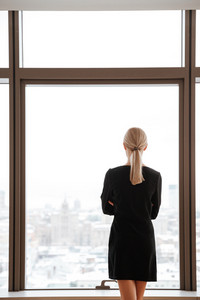 Back view image of young woman worker standing in office while looking at window.