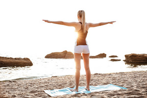 Back view of a beautiful young woman doing stretching exercises during yoga on the beach