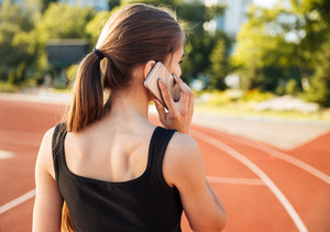 Back view of a female athlete standing on running track and talking on mobile phone