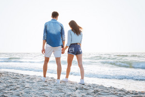 Back view of a happy young couple walking and holding hands at the beach