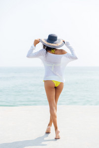 Back view of a happy young woman in bikini and beach hat at the beach