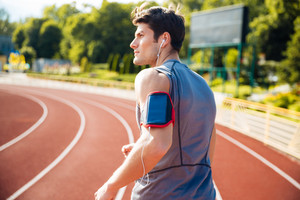 Back view of a male runner listening to music with mobile phone at the stadium