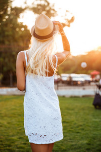 Back view of a young blonde woman wearing white dress and hat posing outdoors at the park