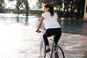 Back view of a young brunette woman riding on bicycle in city street
