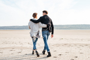 Back view of a young casual couple hugging and walking along beach