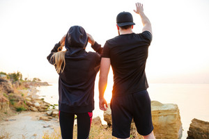Back view of a young sports couple standing on a hill and looking at sunset