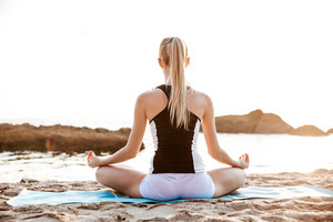 Back view of a young woman sitting in lotus position on beach