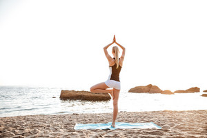 Back view of a young woman standing in yoga pose on one leg on beach
