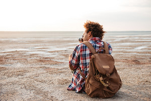 Back view of african young man with backpack sitting and taking photos on the beach
