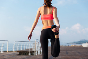 Back view of attractive young sportswoman standing and stretching legs on pier