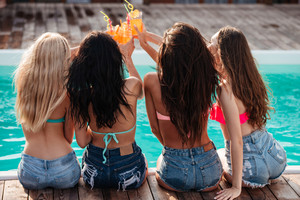 Back view of attractive young women celebrating and toasting at party near swimming pool