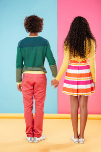 Back view of beautiful african young couple standing and holding hands