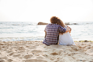 Back view of beautiful young couple sitting and hugging on the beach