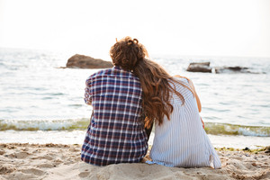 Back view of beautiful young couple sitting together on the beach