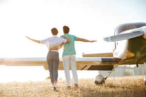 Back view of beautiful young couple walking on field near small airplane