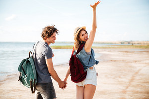 Back view of beautiful young couple with backpacks walking on the beach together
