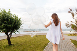 Back view of beautiful young woman in white dress with balloons walking on promenade