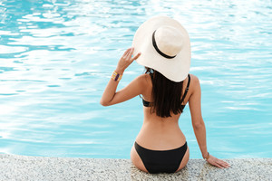 Back view of Brunette woman in swimsuit and hat which sitting near the pool