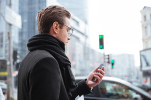 Back view of business man in glasses and warm clothes standing on the street and looking at phone