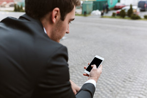Back view of business man in suit with phone outdoors