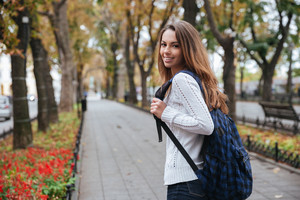 Back view of cheerful attractive young woman with backpack walking in park