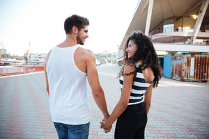 Back view of cheerful young couple standing and holding hands outdoors