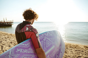 Back view of curly young man surfer