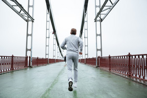 Back view of Elderly Man in gray sportswear running on bridge