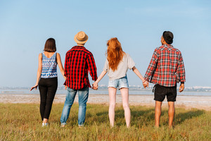 Back view of four happy young people standing and holding hands outdoors