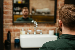 Back view of handsome man getting haircut by hairdresser while sitting in chair. Look at mirror.