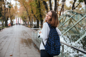 Back view of happy pretty young woman with backpack walking in park