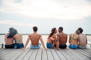 Back view of happy young couples sitting and hugging on pier
