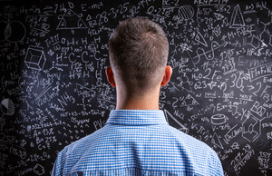 Back view of hipster teacher standing against big blackboard with mathematical symbols and formulas. Studio shot on black background.