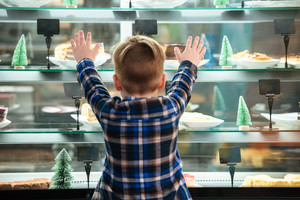 Back view of little boy standing with raised hands and looking at cakes in showcase in cafe