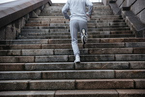 Back view of man in gray sportswear running on stairs. Cropped image