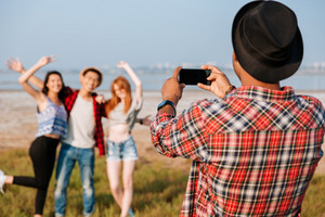 Back view of man in hat taking pictures of his friends with blank screen cell phone outdoors