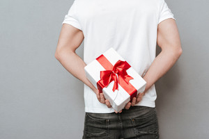 Back view of man with gift. Man holding gift from the back. Cropped image. Isolated gray bakground