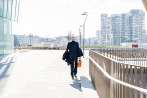 Back view of middle-age businessman holding briefcase walking outdoor in back light - business, entrepreneurship, elegant concept