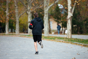 Back view of runner in park. full length image
