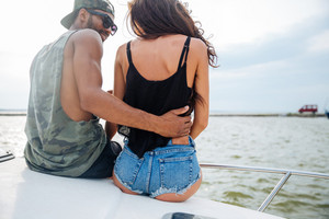 Back view of sensual young couple sitting and embracing on boat
