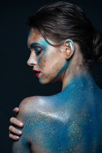 Back view of sensual young woman with blue shining makeup on her body over black background