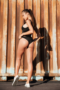 Back view of sexy young woman in black swimwear and white sneakers standing over over rusty metal background