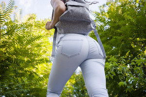 Back view of slim woman in jeans with a backpack walks among green trees in summer, a low angle shooting