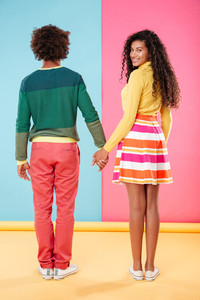 Back view of smiling attractive african young woman standing and holding hands with her boyfriend