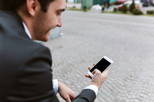 Back view of smiling business man in suit with phone outdoors