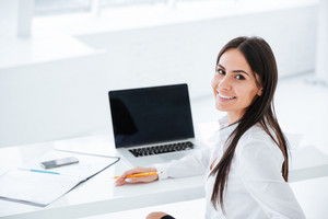 Back view of smiling business woman sitting by the table with laptop and looking at camera in office