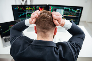 Back view of stressed irritated businessman sitting and working with computer in office