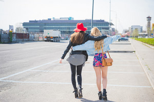 back view of two beautiful blonde and brunette friends walking through the city hugging and having fun - friendship, emancipation concept