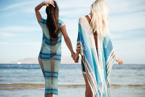 Back view of two women in beachwear which standing on the beach and looking at the sea