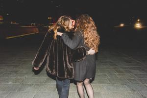 Back view of two young beautiful caucasian women walking outdoor in the city evening, having fun interacting hugging - friendship, interaction, having fun concept